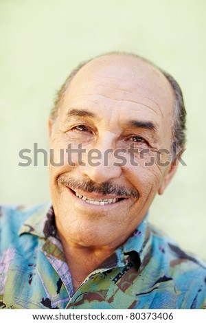 portrait of senior hispanic man looking at camera against green wall and smiling. Horizontal shape, copy space - stock photo