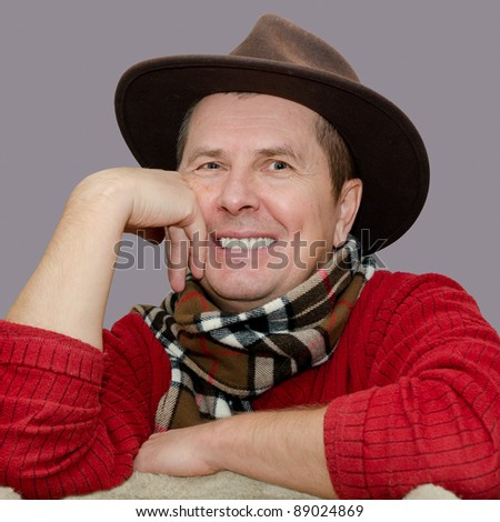 portrait of senior male smiling and wearing a hat - stock photo