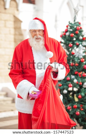Portrait of senior man dressed as Santa Claus putting gift in bag - stock photo