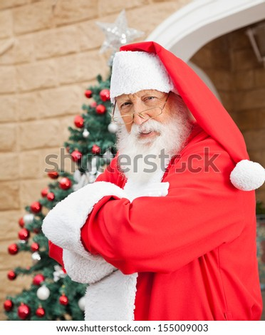 Portrait of senior man dressed as Santa Clause standing arms crossed outside house - stock photo