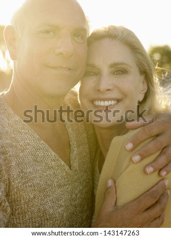 Portrait of senior man embracing woman at sunset on beach - stock photo