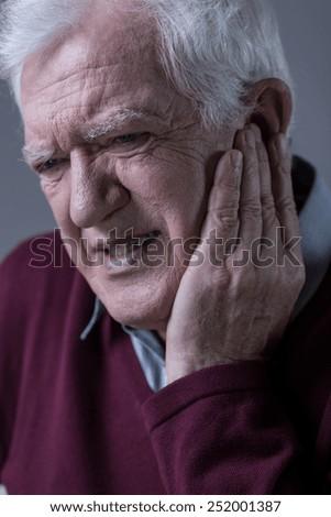 Portrait of senior man having terrible toothache - stock photo
