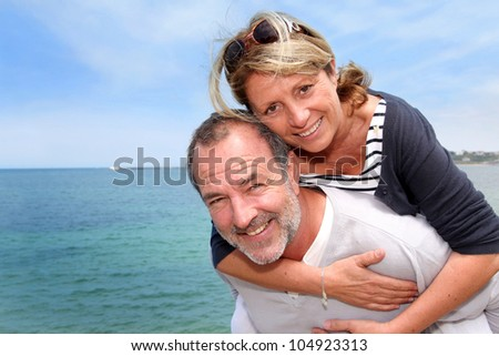 Portrait of senior man holding woman on his back - stock photo