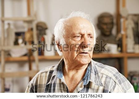 Portrait of senior man in sculptor workshop - stock photo