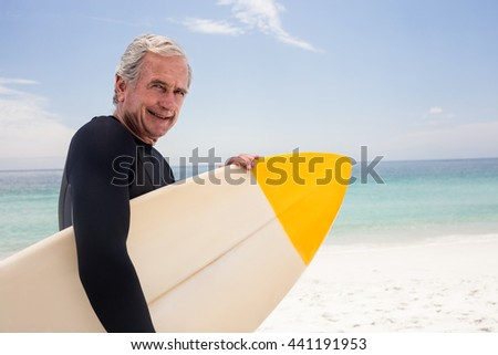 Portrait of senior man in wetsuit holding a surfboard on the beach - stock photo
