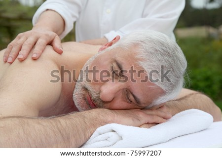 Portrait of senior man laying on a massage bed - stock photo
