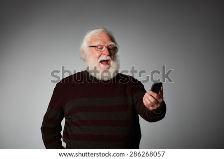 Portrait of senior man reading text message on his smart phone looking excited against grey background - stock photo