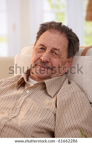 Portrait of senior man resting in armchair at home, looking at camera.? - stock photo