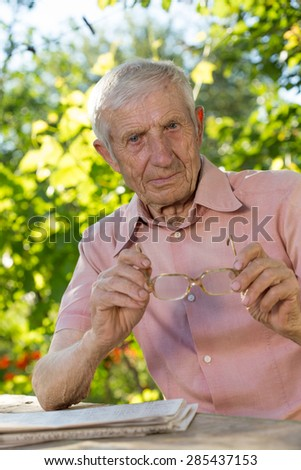 portrait of  senior man  sitting at a table in the garden  - stock photo