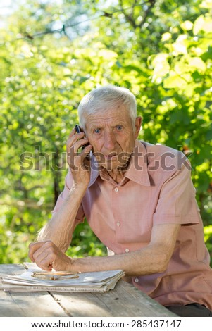 portrait of  senior man  sitting at a table in the garden and talking on the phone  - stock photo