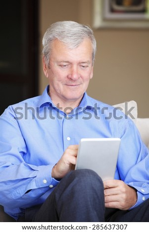 Portrait of senior man sitting at home and holding digital tablet in his hands. Retired man using tablet and touch the screen. - stock photo