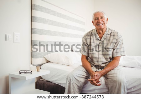 Portrait of senior man sitting on bed and smiling in bedroom - stock photo