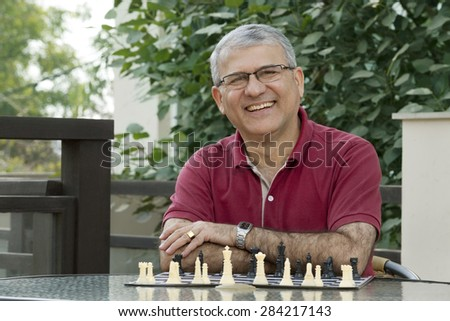 Portrait of senior man smiling while sitting by table with chess board - stock photo