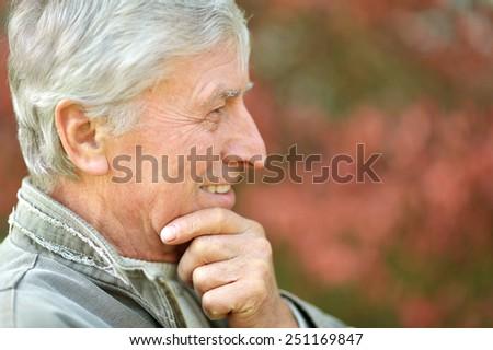 Portrait of senior man thinking about something outdoor - stock photo