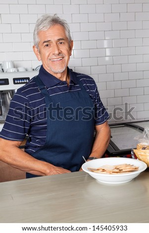 Portrait of senior man with plate of biscuits at counter in supermarket - stock photo