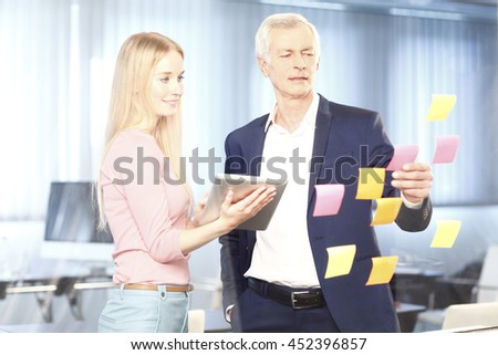 Portrait of senior manager and his young assistant working together while standing at idea board. Beautiful businesswoman holding using digital tablet while executive businessman reading sticky notes. - stock photo