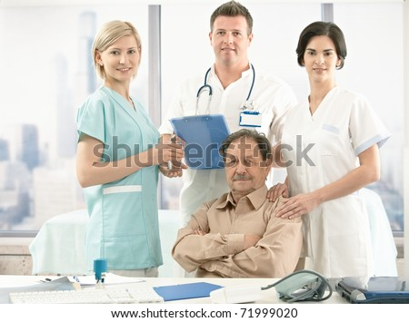 Portrait of senior patient sitting at desk, medical team around, smiling at camera.? - stock photo