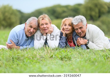 Portrait of senior people laying in grass - stock photo