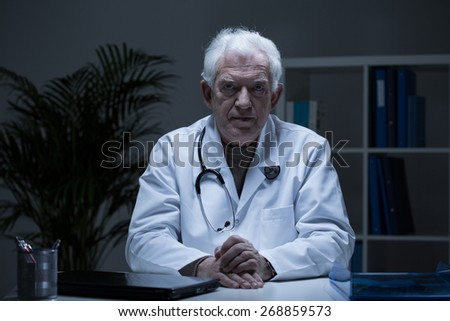 Portrait of senior practitioner in doctor's office - stock photo