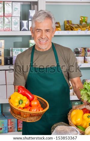 Portrait of senior salesman holding vegetable basket at supermarket - stock photo