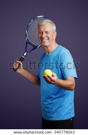 Portrait of senior tennis trainer standing against isolated background while holding in his hand a tennis racket and tennis ball.  - stock photo