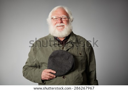Portrait of senior war veteran looking at the camera wearing coat and holding a cap against grey background - stock photo