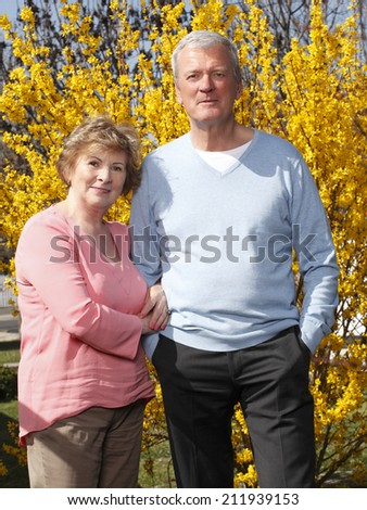 Portrait of senior woman and man standing at garden.  Old people.  - stock photo