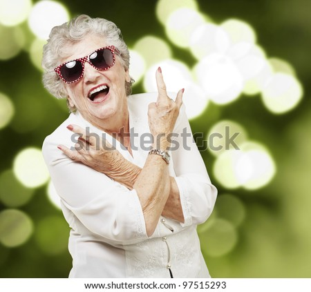 portrait of senior woman doing rock symbol against a abstract background - stock photo