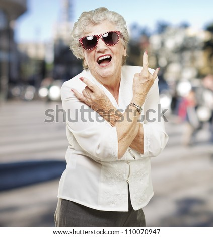 portrait of senior woman doing rock symbol at city background - stock photo
