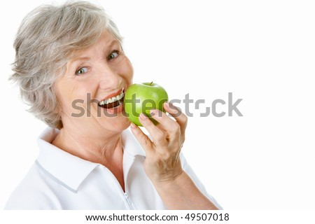 Portrait of senior woman holding an apple by her mouth - stock photo
