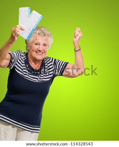 Portrait Of Senior Woman Holding Boarding Pass Cheering On Green Background - stock photo