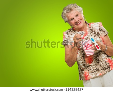 Portrait Of Senior Woman Holding 3d Glasses, Popcorn And Tickets On Green Background - stock photo