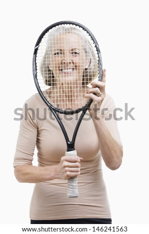 Portrait of senior woman holding tennis racket in front of her face against white background - stock photo