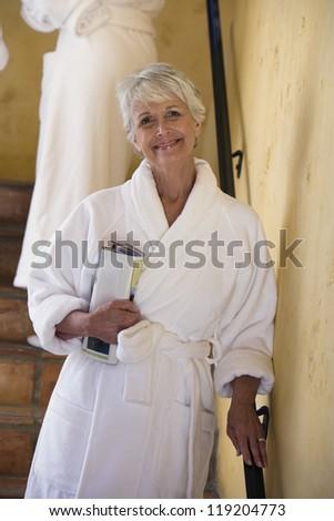 Portrait of senior woman in bathrobe on stairs - stock photo
