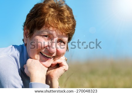 Portrait of senior woman in garden - stock photo