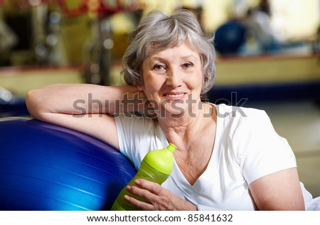 Portrait of senior woman in sportswear looking at camera and smiling - stock photo