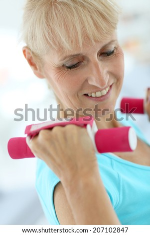 Portrait of senior woman lifting dumbbells - stock photo