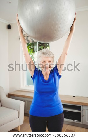 Portrait of senior woman lifting exercise ball while exercising at home - stock photo