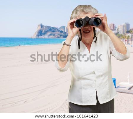 portrait of senior woman looking through a binoculars in the beach - stock photo
