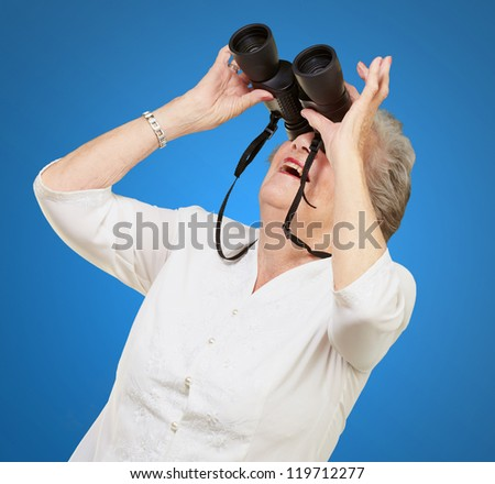 portrait of senior woman looking through a binoculars over blue background - stock photo