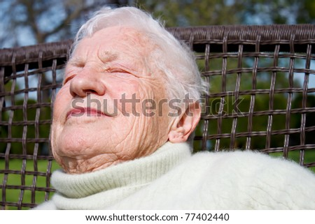 Portrait of senior woman relaxing outside on garden chair - stock photo