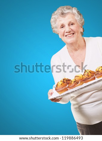 portrait of senior woman showing a chocolate muffin tray over blue background - stock photo