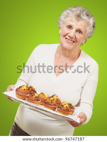 portrait of senior woman showing homemade muffins over green - stock photo