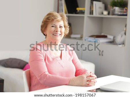 Portrait of senior woman sitting at desk and smiling.  - stock photo