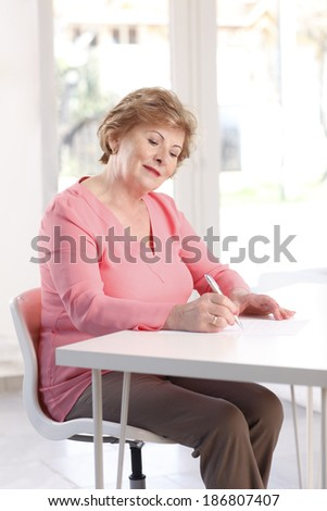 Portrait of senior woman sitting at desk and writing.  - stock photo