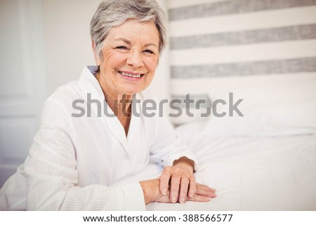 Portrait of senior woman smiling while sitting on bed - stock photo