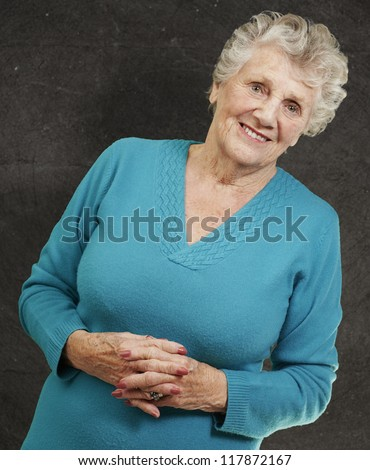 portrait of senior woman standing against a grunge wall - stock photo