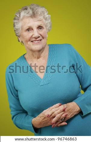 portrait of senior woman standing over yellow background - stock photo