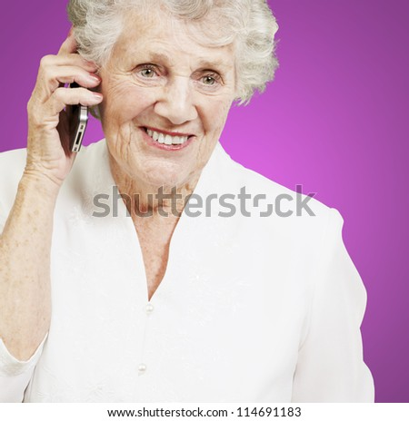 portrait of senior woman talking on mobile over pink background - stock photo