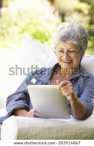 Portrait Of Senior Woman Using Digital Tablet At Home - stock photo